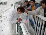 激しい雪と寒さのなか、サインに応じる水野JK